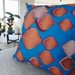 Grå sofa med kvadratisk pude Adisa med flot mønster på klar blå baggrund - Fra Mitomito